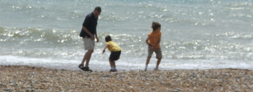 Photo of family on  beach skimming stones 2006